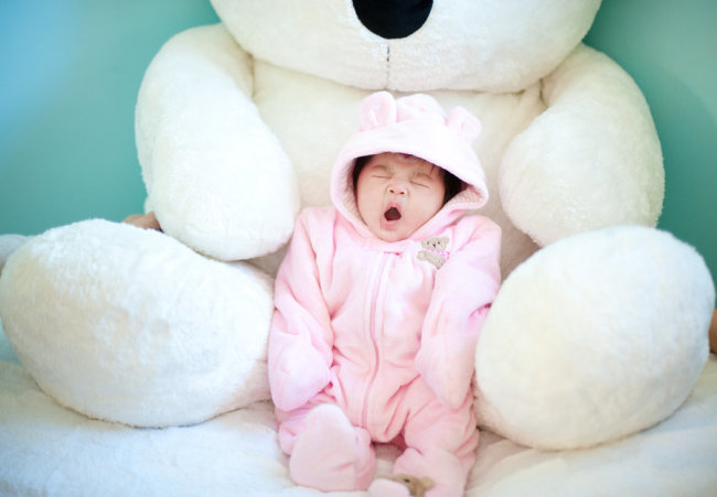 yawning baby with teddy Bear